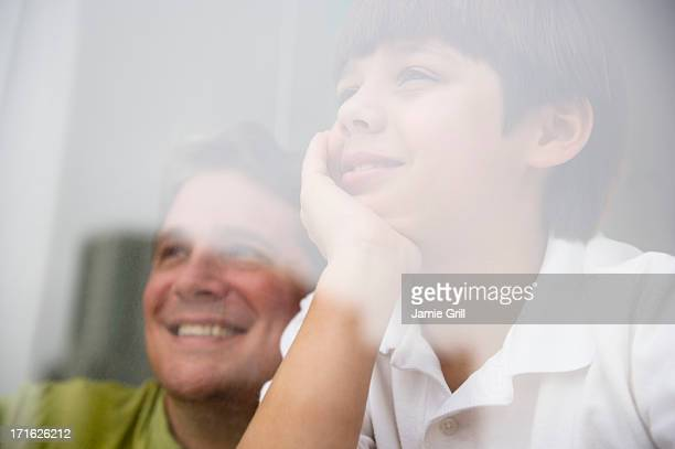 USA, New Jersey, Jersey City, Son (8-9) and father looking through window