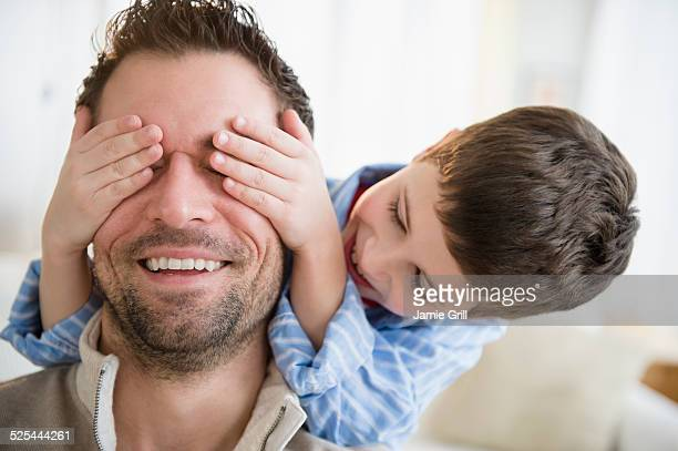 USA, New Jersey, Jersey City, Son (8-9) covering father's eyes