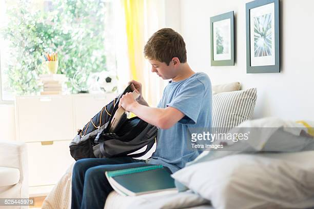USA, New Jersey, Jersey City, Teenage boy (16-17) packing books into backpack