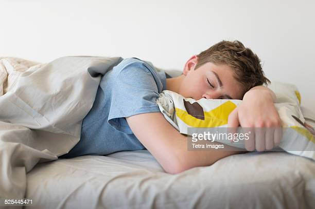 USA, New Jersey, Jersey City, Teenage boy (16-17) sleeping in bed