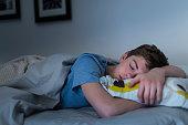 USA, New Jersey, Jersey City, Teenage boy (16-17) sleeping in bed
