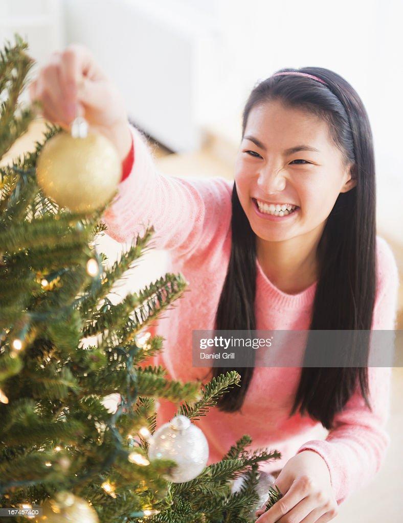 USA, New Jersey, Jersey City, Teenage girl ( 16-17 years) decorating Christmas tree : Stock Photo