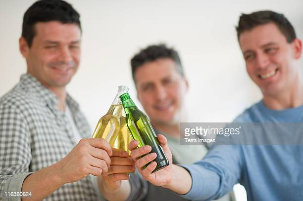 USA, New Jersey, Jersey City, three men toasting with beer