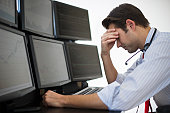 USA, New Jersey, Jersey City, upset financial worker analyzing data displayed on computer screen