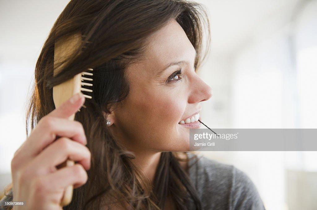 USA, New Jersey, Jersey City, Woman brushing hair