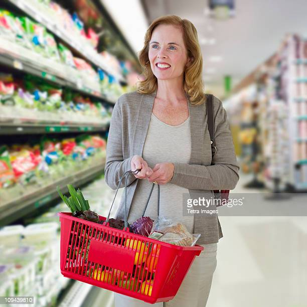 USA, New Jersey, Jersey City, Woman carrying shopping basket in supermarket