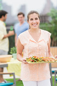 USA, New Jersey, Jersey City, Woman carrying tray with food in garden