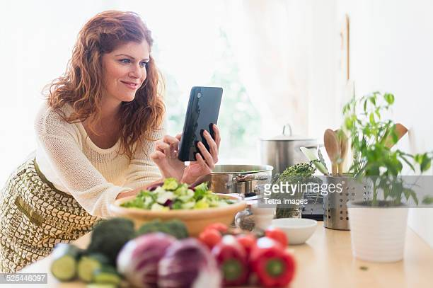 USA, New Jersey, Jersey City, Woman cooking and using digital tablet in kitchen