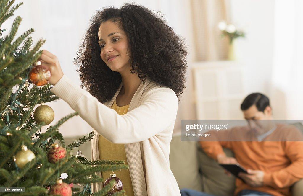 USA, New Jersey, Jersey City, Woman decorating Christmas tree : Stock Photo
