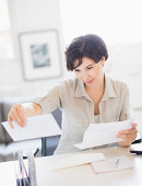 USA, New Jersey, Jersey City, Woman doing paperwork at home office