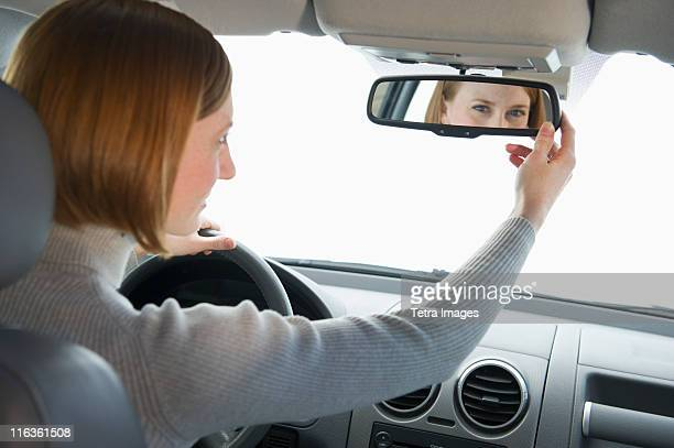 USA, New Jersey, Jersey City, woman driving car and adjusting mirror