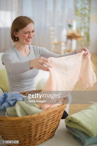 USA, New Jersey, Jersey City, woman folding laundry