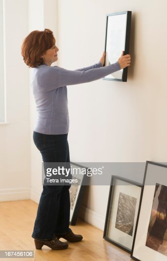 usa new jersey jersey city woman hanging picture on wall stock photo getty images. Black Bedroom Furniture Sets. Home Design Ideas