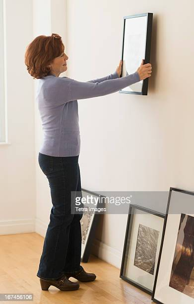 USA, New Jersey, Jersey City, Woman hanging picture on wall