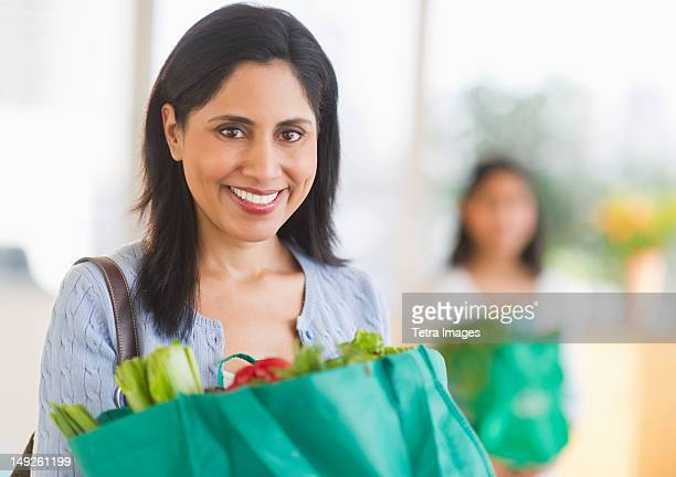 USA, New Jersey, Jersey City, Woman holding bag of fresh vegetables