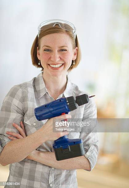 USA, New Jersey, Jersey City, woman holding drill, portrait