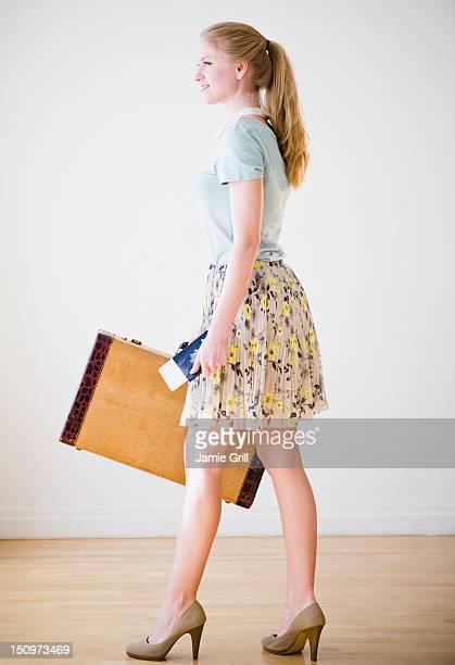 USA, New Jersey, Jersey City, Woman holding suitcase and passport
