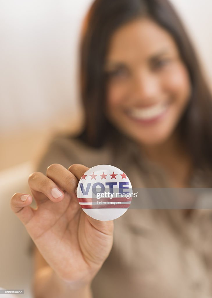 USA, New Jersey, Jersey City, Woman holding vote button : Stock Photo
