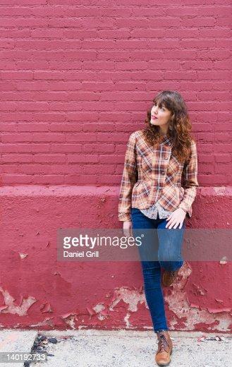 USA, New Jersey, Jersey City, Woman leaning against purple brick wall