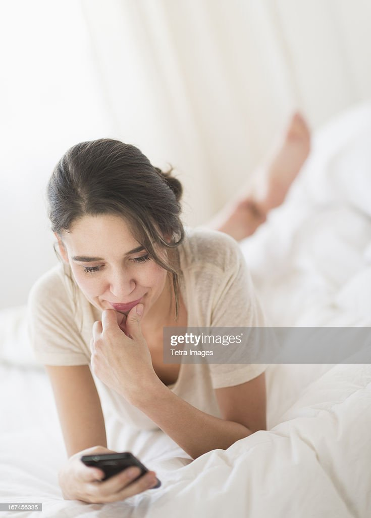 USA, New Jersey, Jersey City, Woman lying in bed and text messaging : Stock Photo