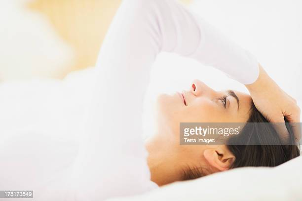 USA, New Jersey, Jersey City, Woman lying in bed