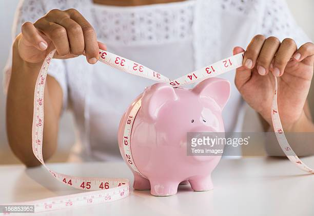 USA, New Jersey, Jersey City, Woman measuring piggy bank