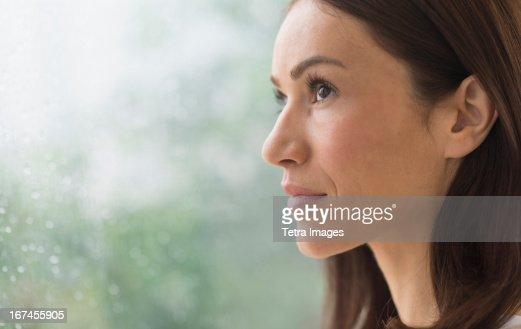 USA, New Jersey, Jersey City, Woman next to rainy window : Stock Photo