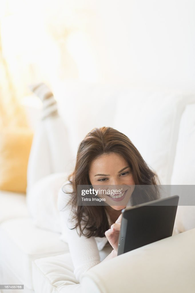 USA, New Jersey, Jersey City, Woman on sofa using tablet pc : Stock Photo