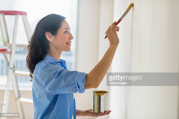 USA, New Jersey, Jersey City, Woman painting wall at home