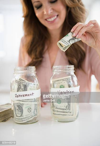 USA, New Jersey, Jersey City, Woman putting money in jar