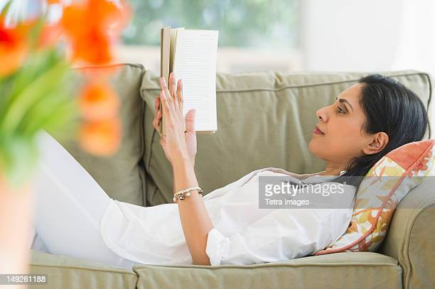 USA, New Jersey, Jersey City, Woman reading book on sofa