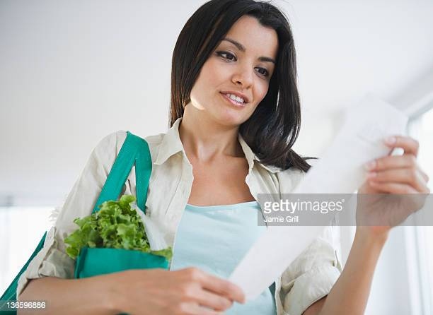 USA, New Jersey, Jersey City, Woman reading receipt