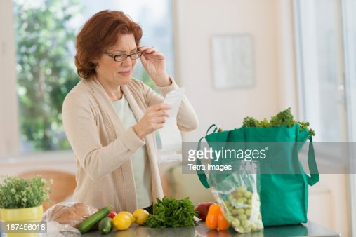 USA, New Jersey, Jersey City, Woman reading shopping list in kitchen : Stock Photo