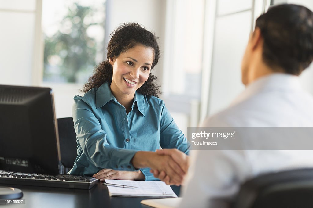 USA, New Jersey, Jersey City, Woman shaking hand with man at desk : Stock Photo