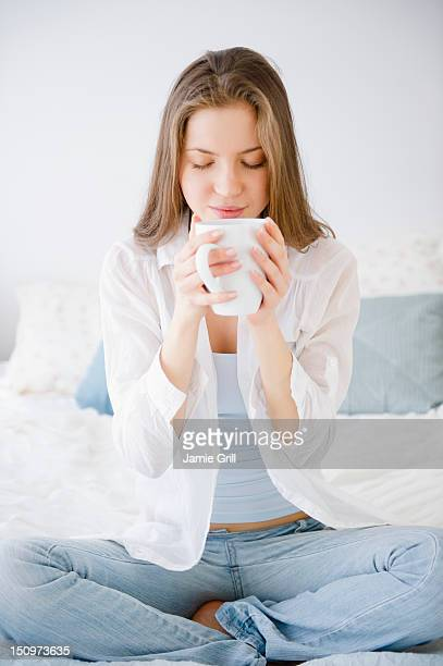USA, New Jersey, Jersey City, Woman sitting on bed drinking coffee