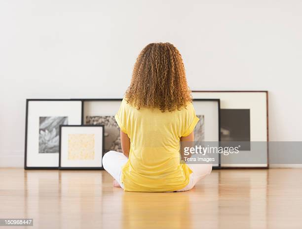 USA, New Jersey, Jersey City, Woman sitting on floor looking at artworks