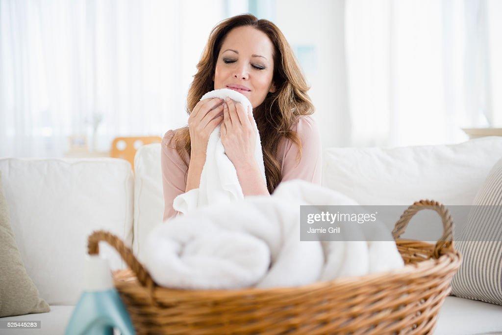 USA, New Jersey, Jersey City, Woman smelling washed laundry