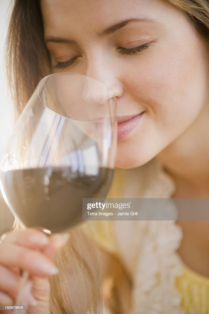 USA, New Jersey, Jersey City, Woman smelling wine
