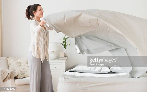 USA, New Jersey, Jersey City, Woman spreading sheet on bed
