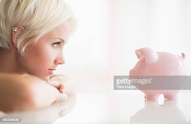 USA, New Jersey, Jersey City, Woman staring at piggy bank