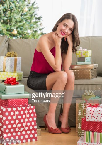 USA, New Jersey, Jersey City, Woman surrounded with christmas gifts sitting on sofa : Stock Photo