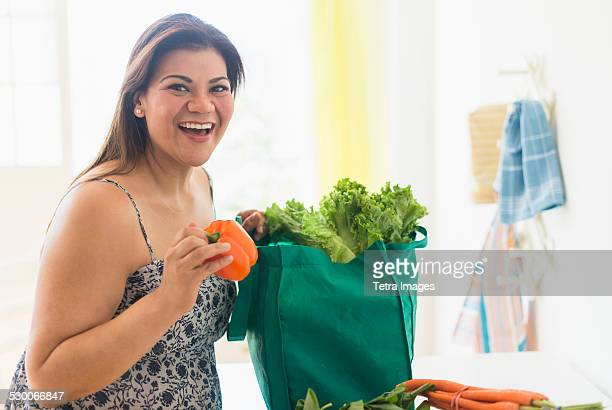 USA, New Jersey, Jersey City, Woman taking out vegetables of grocery bag