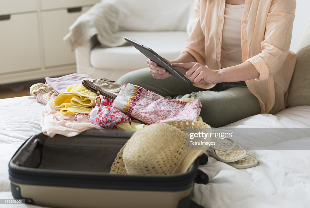 USA, New Jersey, Jersey City, Woman using digital tablet while packing suitcase