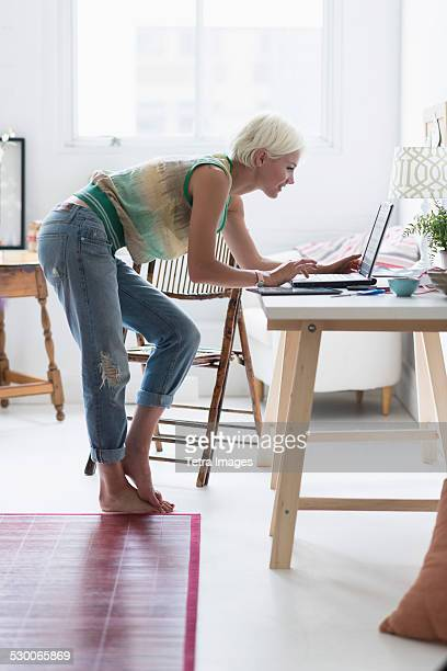 USA, New Jersey, Jersey City, Woman using laptop and at home