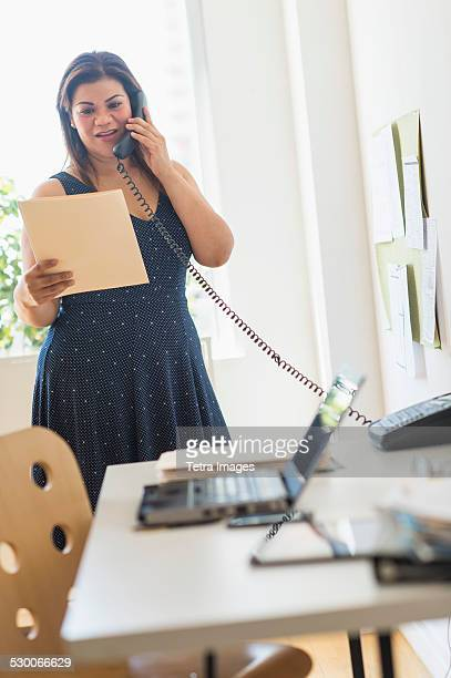 USA, New Jersey, Jersey City, Woman using telephone in office