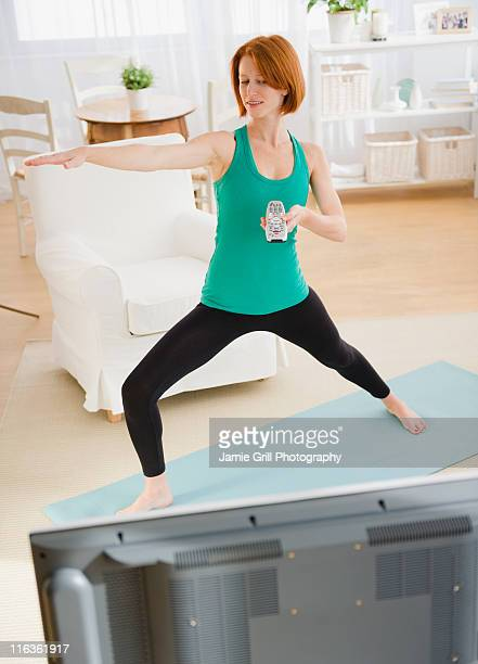 USA, New Jersey, Jersey City, woman watching tv and exercising