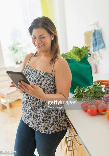 USA, New Jersey, Jersey City, Woman with tablet pc in kitchen