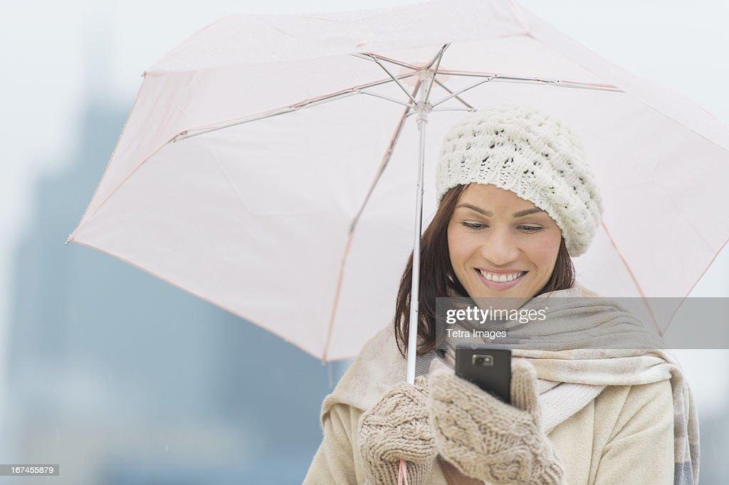USA, New Jersey, Jersey City, Woman with umbrella using phone : Stock Photo