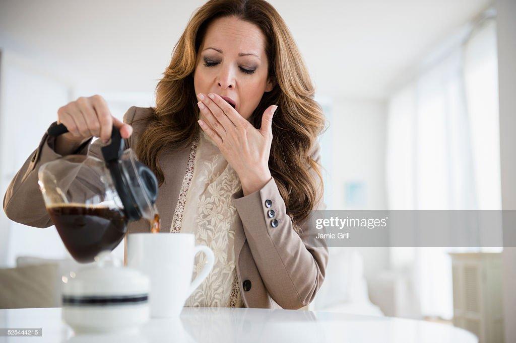 USA, New Jersey, Jersey City, Yawnging woman pouring coffee