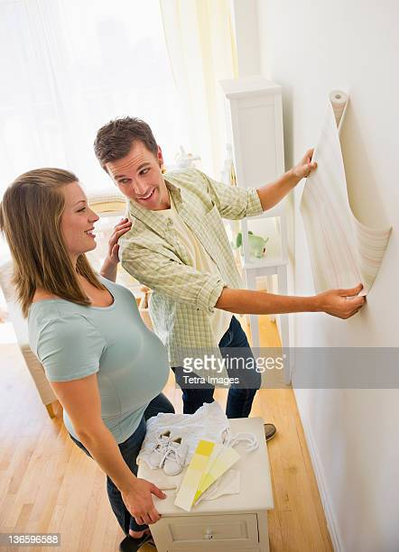 USA, New Jersey, Jersey City, Young couple choosing wallpaper for nursery